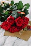 Un bouquet des roses rouges, enveloppe avec la félicitation sur un fond de toile Image libre de droits