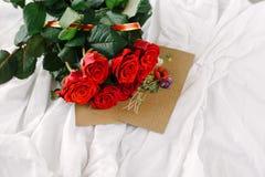 Un bouquet des roses rouges, enveloppe avec la félicitation sur un fond de toile Images stock