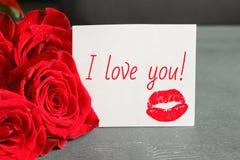 Un bouquet des roses rouges et d'une feuille de livre blanc avec l'inscription je t'aime, sur un fond noir en bois photo stock