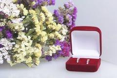 Un bouquet des supports de fleurs secs dans un verre sur une surface blanche Est tout près une boîte ouverte de velours avec un c Photo stock