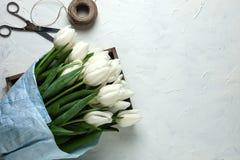 Un bouquet des tulipes blanches en papier d'emballage bleu en boîte en bois avec des ciseaux et ficelle sur un fond concret blanc Image libre de droits