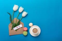 Un bouquet des tulipes blanches et d'une tasse de café avec une note d'amour et de macarons sur un fond bleu photos libres de droits