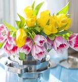 Un bouquet des tulipes de ressort de couleur jaune et rose Les fleurs dans de nouvelles casseroles assiettes carte Cadeau photo libre de droits