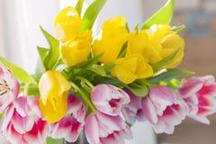 Un bouquet des tulipes de ressort de couleur jaune et rose Les fleurs dans de nouvelles casseroles assiettes carte Cadeau photographie stock