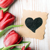 Un bouquet des tulipes et de la carte ornementale avec le coeur Photographie stock
