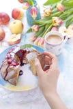Un bouquet des tulipes fraîches Petit gâteau à la maison doux avec du sucre Café dans une tasse Pommes sur la table La main tient Images libres de droits