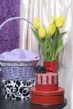 Un bouquet des tulipes jaunes se tient dans un vase en verre enveloppé dans un ruban rouge attaché à un arc Tout près il y a des  photo stock