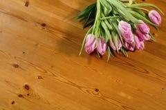 Un bouquet des tulipes roses sur un beau fond en bois rebobiné avec une ficelle de fil de métier Image stock