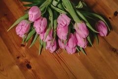 Un bouquet des tulipes roses sur un beau fond en bois rebobiné avec une ficelle de fil de métier Photo stock