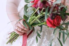 Un bouquet nuptiale dans les mains de la jeune mariée Roses rouges Photos libres de droits