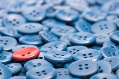 Un bouton rouge sur un tas des boutons bleus Image stock