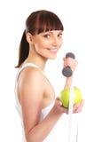 Un brunette joven con una pesa de gimnasia y una manzana Foto de archivo
