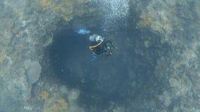 Un buceador va dentro de una dolina bajo el agua almacen de metraje de vídeo