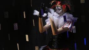 Un bufón de sexo femenino con maquillaje blanco y negro con una expresión seria en su cara está entreteniendo a la muchedumbre almacen de metraje de vídeo