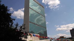 United Nations building in New York City. UN building in NYC with flags in front waving in the wind and white clouds reflected in the glass front stock footage