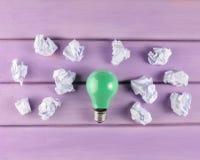 Un bulbo incandescente coloreado y bolas arrugadas del Libro Blanco en una tabla de madera púrpura Concepto ideológico, visión su imagen de archivo libre de regalías