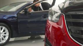 Un buon venditore delle automobili conduce il cliente alla sua automobile immagine stock libera da diritti