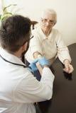 Un bureau privé du ` s de docteur Docteur examinant une main du ` s de dame âgée Images libres de droits