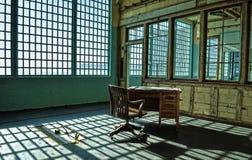 Un bureau ruiné et une chaise dans une installation abandonnée de prison photographie stock