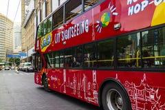 Un bus di giro rosso che passa vicino fotografie stock