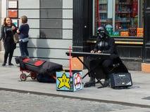 Un busker en un Darth Vader que el traje en la ciudad de Dublín maneja su comercio mientras que siendo ignorado por un par de muj Imagen de archivo libre de regalías