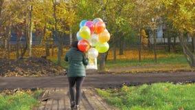 Un a cámara lenta de una mujer que camina con los globos en un día hermoso del otoño almacen de metraje de vídeo