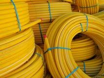 Un câble électrique jaune lumineux est relié aux bobines énormes, dessinées par un ruban vert, un fond industriel de concepteur Images stock