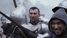 Un caballero en armadura se est? colocando en el campo de batalla mientras que la gente est? luchando almacen de metraje de vídeo