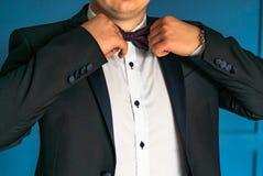 Un caballero en lujoso en una chaqueta negra y una camisa blanca corrige la corbata de lazo al lado de sus manos imágenes de archivo libres de regalías