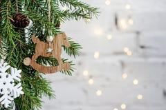 Un caballo de madera en un árbol de navidad en un fondo de luces Imágenes de archivo libres de regalías