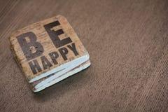Un caboteur en pierre sur une lecture en bois de surface de table soit heureux Photo stock