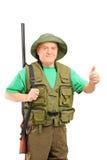 Un cacciatore maturo che tiene un fucile e che dà un pollice su Fotografia Stock Libera da Diritti
