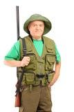 Un cacciatore maturo che tiene un fucile e che esamina macchina fotografica Immagine Stock