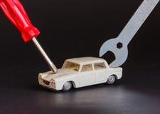 Un cacciavite e una chiave sono messi a fuoco su un modello di un'automobile Fotografia Stock Libera da Diritti