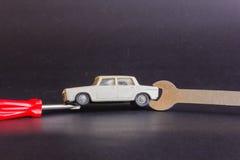 Un cacciavite e una chiave sono messi a fuoco su un modello di un'automobile Fotografia Stock