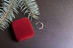 Un cadeau à aimé Boîte fermée de velours de couleur rouge avec des boucles d'oreille d'or Est tout près un anneau d'or Sur un fon Image libre de droits