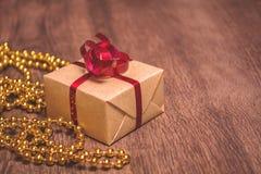 Un cadeau, attaché avec un ruban rouge et enveloppé en papier d'emballage sur un fond en bois Image stock