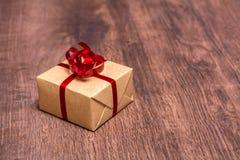 Un cadeau, attaché avec un ruban rouge et enveloppé en papier d'emballage sur un fond en bois Photo stock