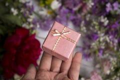 Un cadeau dans une boîte de rose de carton, autour de beaucoup de cadeau rose et lilas d'andA dans une boîte de rose de carton, a Images libres de droits