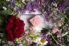 Un cadeau dans une boîte de rose de carton, autour de beaucoup de cadeau rose et lilas d'andA dans une boîte de rose de carton, a Images stock