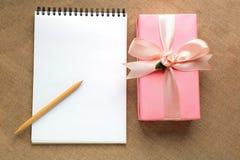 Un cadeau dans une boîte rose décorée du ruban en soie, une page blanche o Photographie stock