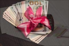 Un cadeau dans une enveloppe et une calculatrice roses de fond Photographie stock