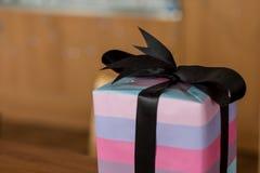 Un cadeau de Noël avec l'arc noir et le papp de emballage rose pourpre Images libres de droits