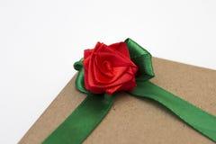 Un cadeau enveloppé en papier et attaché avec un ruban vert avec une fleur rouge de rose Photo libre de droits