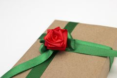 Un cadeau enveloppé en papier et attaché avec un ruban vert avec une fleur rouge a monté Photo libre de droits