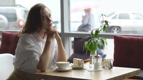 Un café de consumición de la mujer hermosa joven en un café la mujer joven en negocio viste en una hora de la almuerzo almacen de video