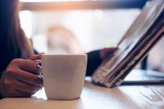 Un café de journal de lecture de femme d'affaires, de se tenir et de boissons photo libre de droits