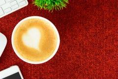 Un café de latte avec du lait de coeur d'art sur la table rouge de bureau de à Image libre de droits