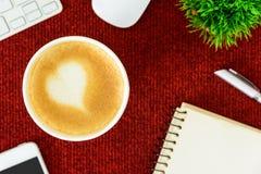 Un café de latte avec du lait de coeur d'art sur la table rouge de bureau de à Image stock