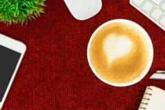 Un café de latte avec du lait de coeur d'art sur la table rouge de bureau de à Images stock